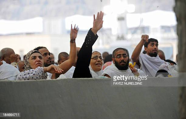 Muslim pilgrims throw pebbles at pillars during the Jamarat ritual the stoning of Satan in Mina near the holy city of Mecca on October 15 2013...