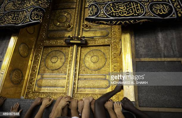 Muslim pilgrims touch Islam's holiest shrine the Kaaba at the Grand Mosque in the Saudi holy city of Mecca late on September 21 2015 The annual hajj...