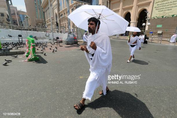 Muslim pilgrims use umbrellas to protect themselves from the sun as they walk in a street in Saudi Arabia's holy city of Mecca on August 19 during...