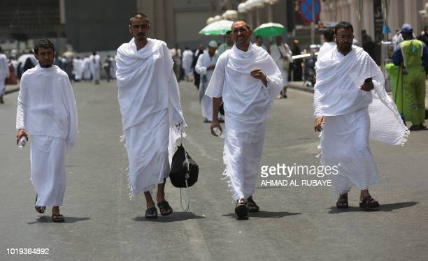 Muslim pilgrims walk in a street in Saudi Arabia's holy city of Mecca on August 19 during the first day of the annual Hajj pilgrimage Muslims from...