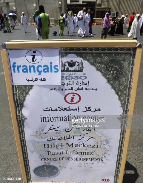 Muslim pilgrims walk past an information of the poster of the translation bureau in the Saudi holy city of Mecca ahead of the start of the Hajj...