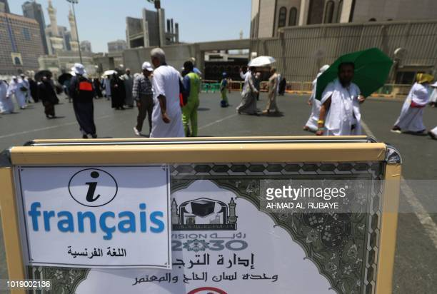 Muslim pilgrims walk past an information poster of the translation bureau in the Saudi holy city of Mecca ahead of the start of the Hajj pilgrimage...