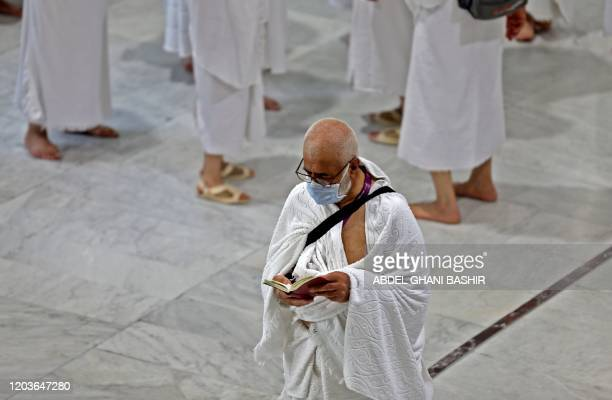 Muslim pilgrims wear masks at the Grand Mosque in Saudi Arabia's holy city of Mecca on February 27, 2020. - Saudi Arabia suspended visas for visits...
