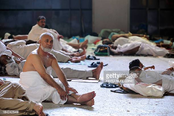 A muslim piligrim looks on as others sleep on ground waiting for performing morning prayer in Mecca's Grand Mosque on October 13 as hundreds of...