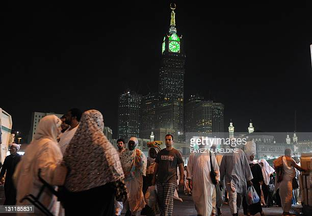 Muslim piligrims walk in front of the clock tower of Mecca after performing the evening prayer in the holy city's Grand Mosque on November 2 2011 The...