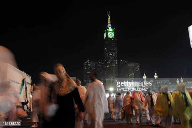 Muslim piligrims walk in front of the clock tower of Mecca after performing the evening prayer in the holy city's Grand Mosque on November 2 2011...