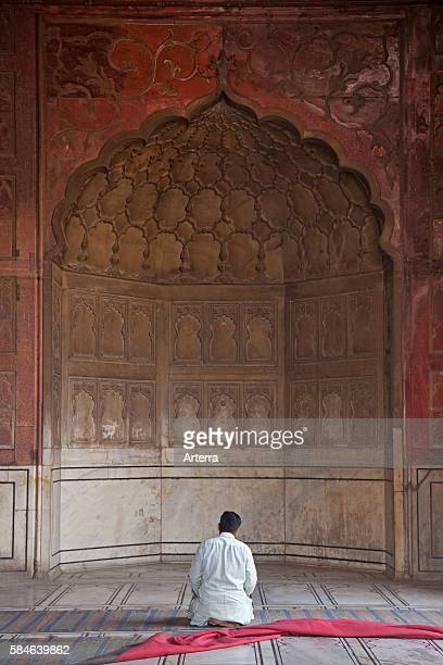 Muslim praying in the prayer area inside the / Jama Masjid mosque in Old Delhi India
