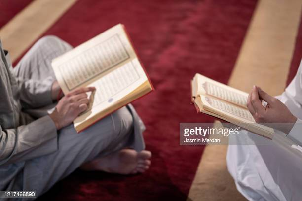 muslim praying inside mosque reading koran - koran stock pictures, royalty-free photos & images