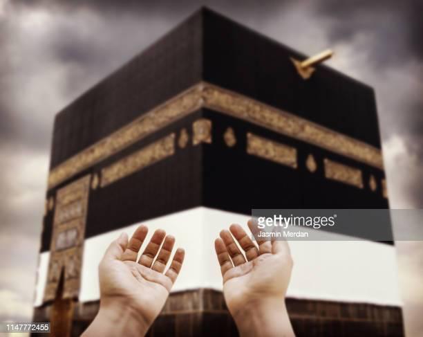 muslim praying to allah in front of kaaba - allah stock-fotos und bilder