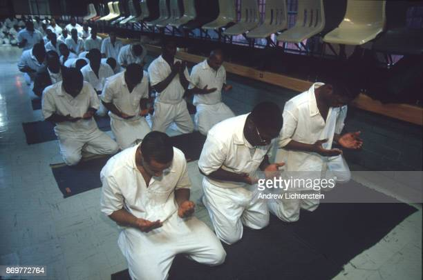 Muslim prisoners pray in a visiting room at the Ferguson Unit a Texas State Prison on January 15 1997 in Midway Texas