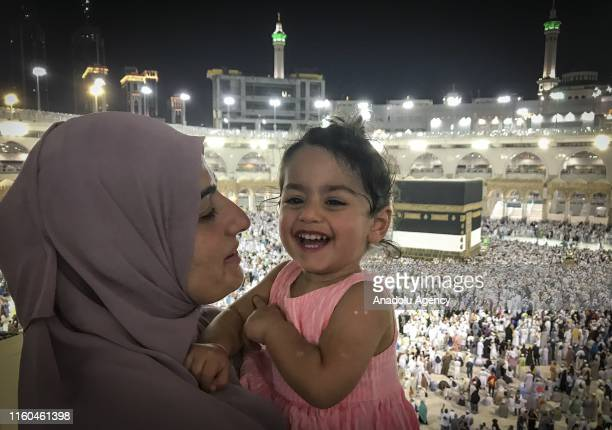 Muslim prospective Hajj pilgrim carries a child as Muslims circumambulate the Kaaba in the background at Masjid alHaram in Mecca Saudi Arabia on...