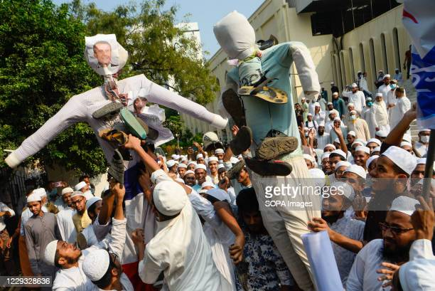 Muslim protesters display effigies of French President Macron while they hang shoes on the effigies during the demonstration. Thousands of Muslim...