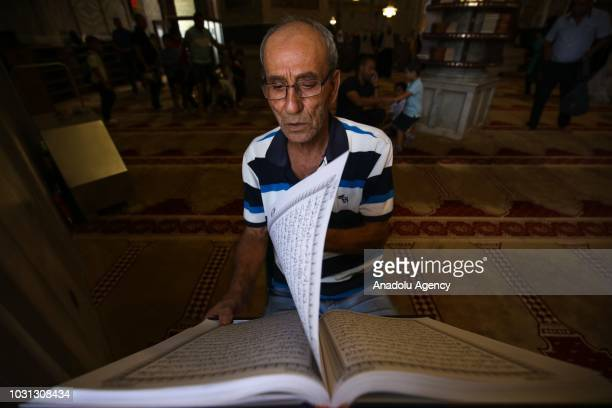 A muslim recites from the holy Qur'an during the 1 Muharram 1440 Hijriah celebrations marking Islamic new year after performing noon prayer at the...