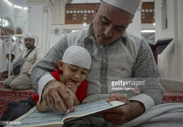 Muslim recites holy Quran with a child at Masjid al-Qiblatayn after Muslims completed the hajj pilgrimage in Medina, Saudi Arabia on August 16, 2018....
