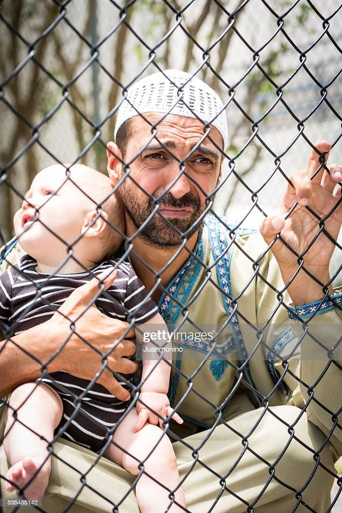 Muslim refugee holding his baby : Stock Photo