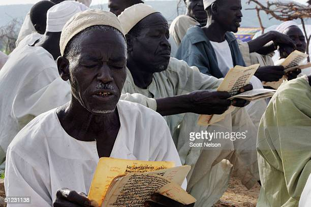 Muslim refugees from the Darfur region of Sudan communaly read koranic verses August 28 2004 in the spontaneous overflow camp outside the Bredjing...