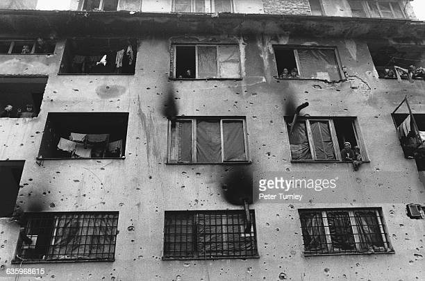 Muslim refugees lean out of the windows of their dingy apartment building covered with evidence of shelling After the fall of Communism in 198990...