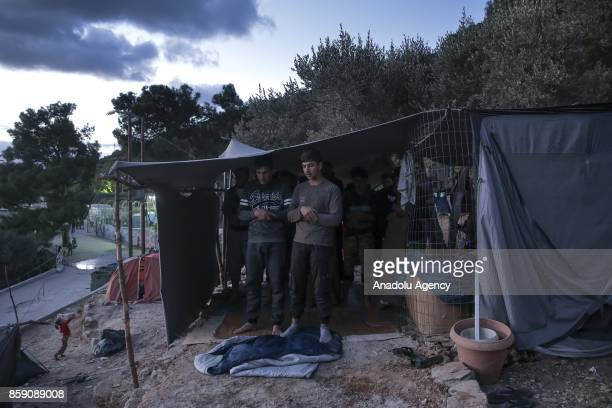 Muslim refugees perform a prayer under a summer tent in a forestland in Samos Greece on October 8 2017 Hundreds of refugees sheltered in the forest...