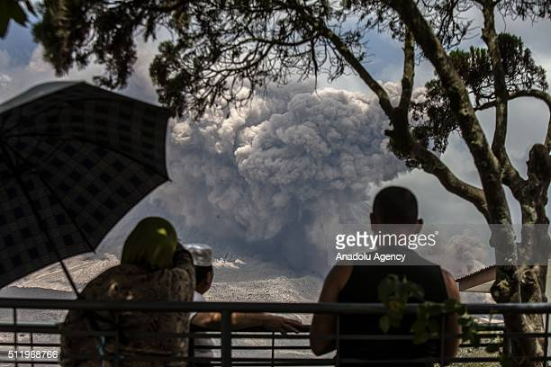 Muslim residents are seen as volcanic smoke and ash rise from Mount Sinabung during an eruption at Gamber village in Karo North Sumatra Indonesia on...