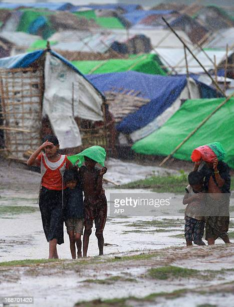 Muslim Rohingya kids walk in front of their tent as rain falls at Mansi Internally Displaced Persons camp in Sittwe on May 14 2013 Boats carrying...