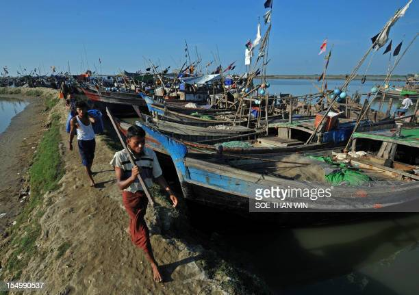 Muslim Rohingya men walk past fishing boats near the temperory relief camp at the Bawdupha Internally Displaced Persons camp located on the outskirts...