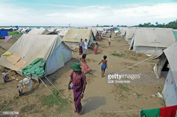 Muslim Rohingya people walk around the Bawdupha Internally Displaced Persons camp on the outskirts of Sittwe, the capital of Myanmar's western...