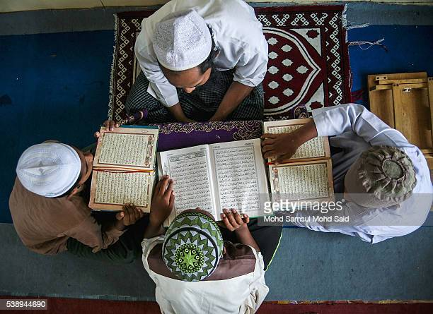 Muslim Rohingya refugees read the Koran inside the Madrasah during the holy month of Ramadan on June 9 2016 in Klang outside Kuala Lumpur Malaysia...
