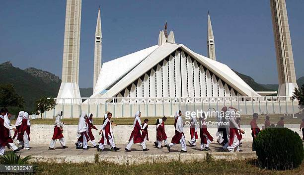 Muslim school girls walk past the Faisal Mosque on their way for a visit in Islamabad Pakistan