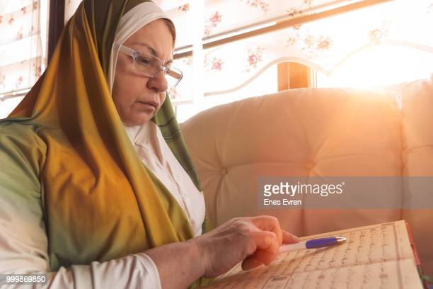 muslim senior woman reading quran - arabic script stock pictures, royalty-free photos & images