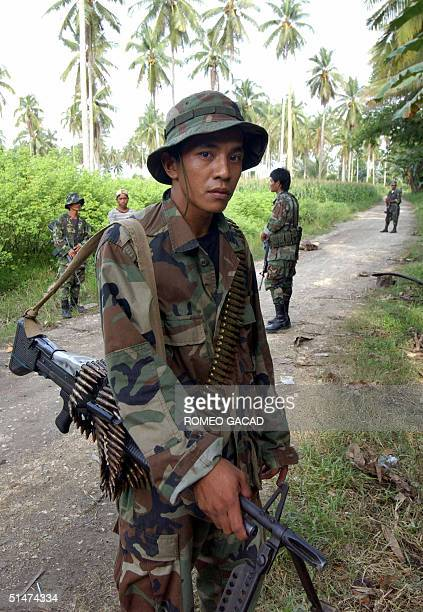 Muslim separatist guerrillas of the Moro Islamic Liberation Front stands at a road block outside the rebels' base in Camp Darapanan in Maguindanao...