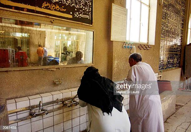 Muslim Shias attend the traditional wash before Friday prayer in a mosque June 6 2003 in Saddam City Baghdad