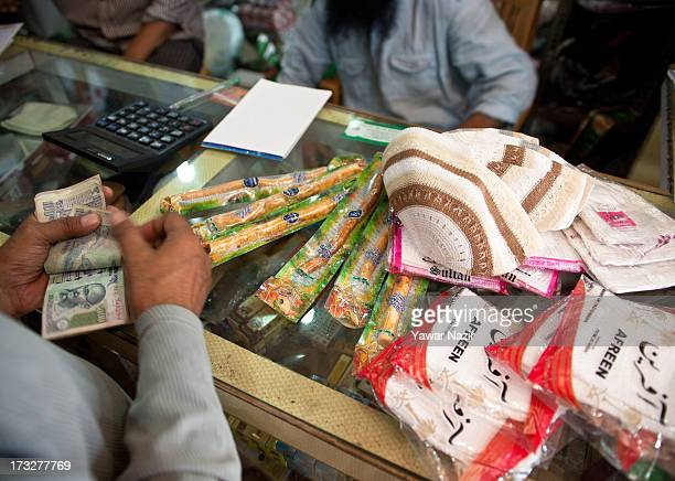 Muslim shopkeeper sells caps and twigs for teeth cleaning during prayer to Muslim customers on the first day of holy month of Ramadan on July 11 2013...