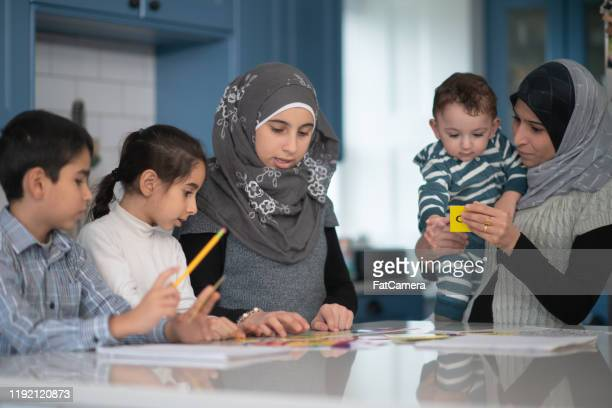 muslim siblings working on homework stock photo - refugee stock pictures, royalty-free photos & images