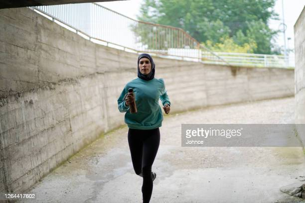 muslim sporty woman is jogging - religious dress stock pictures, royalty-free photos & images