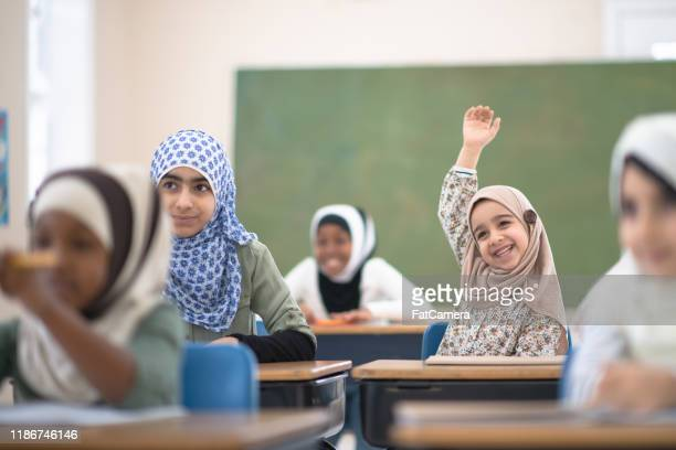muslim student raises her hand for a question stock photo - islam stock pictures, royalty-free photos & images
