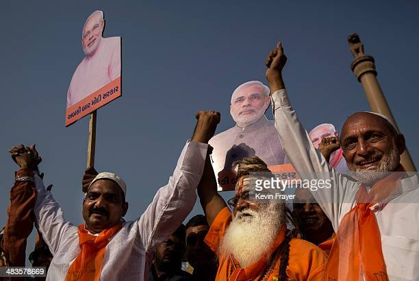 Muslim supporters of Bharatiya Janata Party leader Narendra Modi and a Hindu holy man hold placards at an event before Modi filed his nomination...
