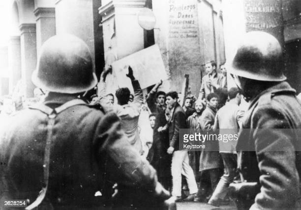 Muslim supporters of the National Liberation Front demonstrate in the Casbah Algiers in front of a cordon of French troops
