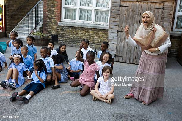 A Muslim teacher at Millfields Community School cheers her Reception Year pupils on during a practice race for their sports day which was due to take...