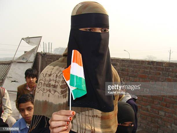 Muslim teacher in niqab/hijab holds India's national flag Tricolor on the occasion of India's Republic Day celebrations in a school where she is the...