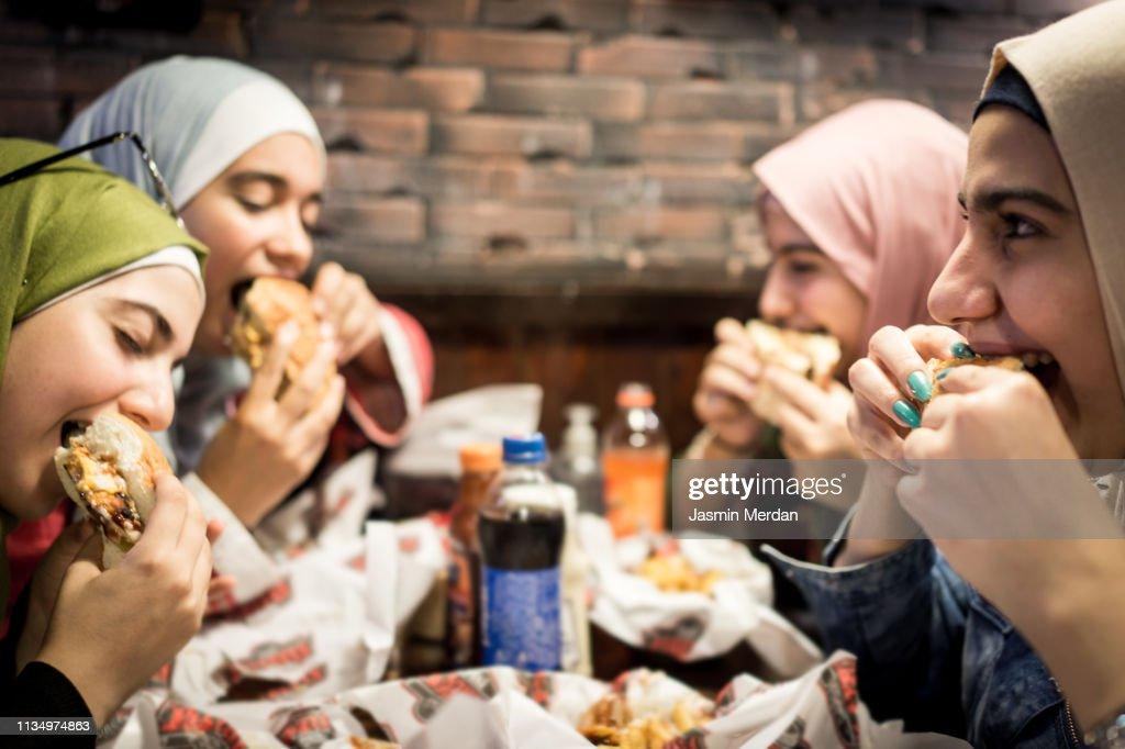 Muslim teenage girls having a lunch break together in restaurant : Stockfoto