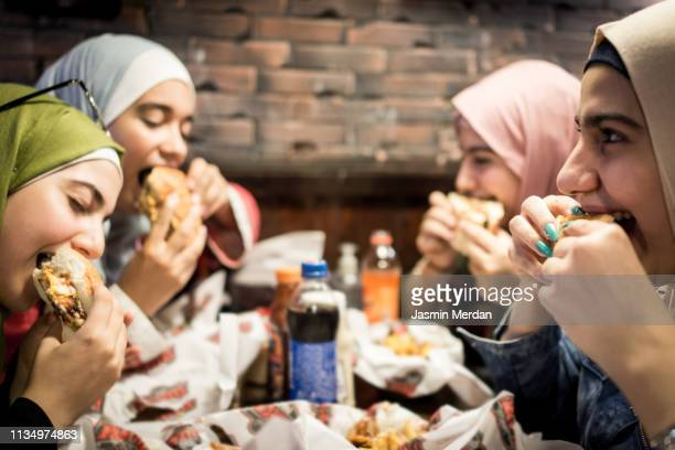 muslim teenage girls having a lunch break together in restaurant - jordan middle east stock pictures, royalty-free photos & images