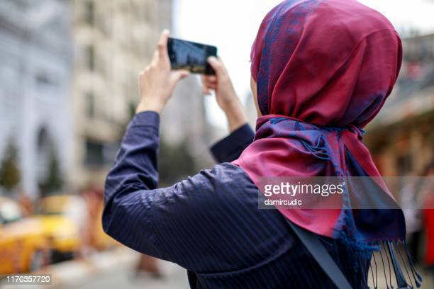 muslim tourist taking photos in the city - damircudic stock photos and pictures