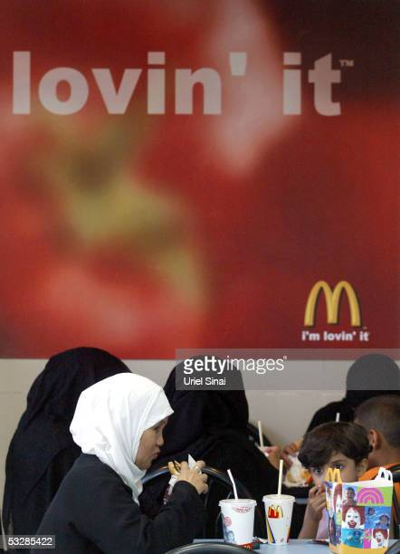 Muslim tourists eat in a McDonald's restaurant on July 25 2005 in the Egyptian Red Sea resort of Sharm elSheikh With foreign tourists cutting short...