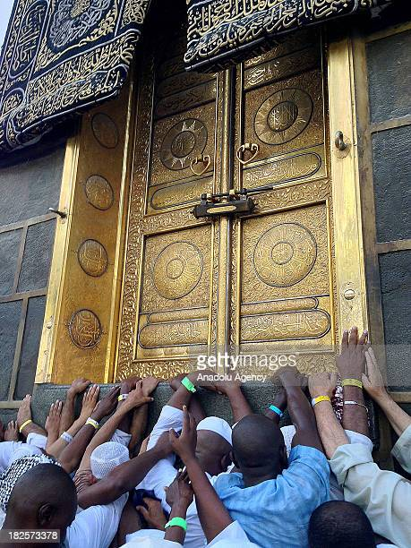 Muslim trying to touch the golden entrance door of Kaaba in Mecca on September 28 2013 in Saudi Arabia Muslims circumambulate Kaaba the Sacred House...