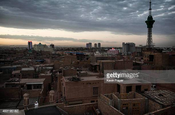 Muslim Uyghur muezzin shouts the call to prayer from the rooftop of a local mosque on July 31, 2014 as old Kashgar can be seen, Xinjiang Uyghur...