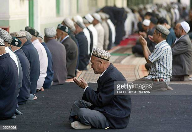 Muslim Uygurs pray during afternoon prayers at the Idkah Mosque in Kashgar 17 September 2003 in northwest China's Xinjiang province Laying west of...