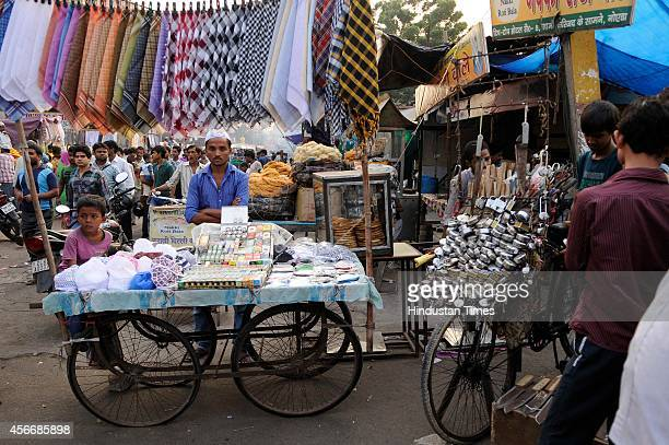 Muslim vendor waits for customers as he sells religious items outside a mosque ahead of the sacrificial Eid al-Adha festival on October 5, 2014 in...