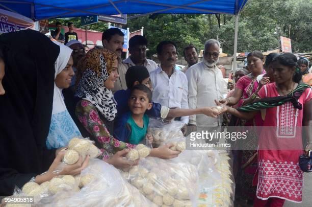 Muslim volunteers of Rijwani Masjid Talwar Wabut trust and young circle distributed Laddoo's to Pilgrims at Ganj peth on July 8 2018 in Pune India...