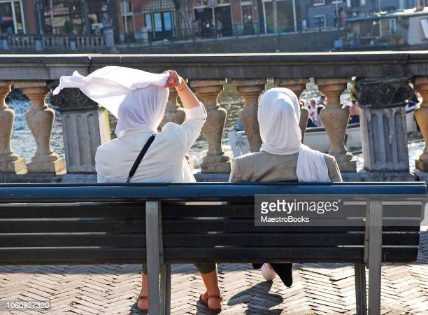muslim woman adjusting her headscarf in the street. - islamophobia stock pictures, royalty-free photos & images