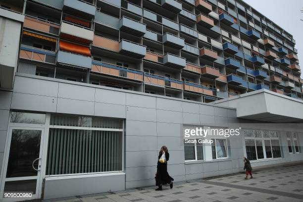 Muslim woman and child walk among apartment buildings in Sachsendorf district where many refugees from Syria and Afghanistan have settled on January...